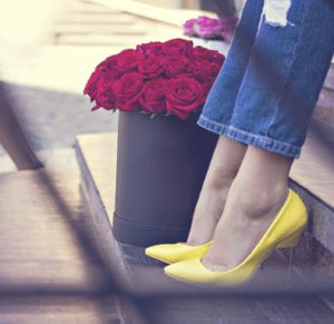 The bouquet of red roses and female legs in jeans and yellow shoes with heels.